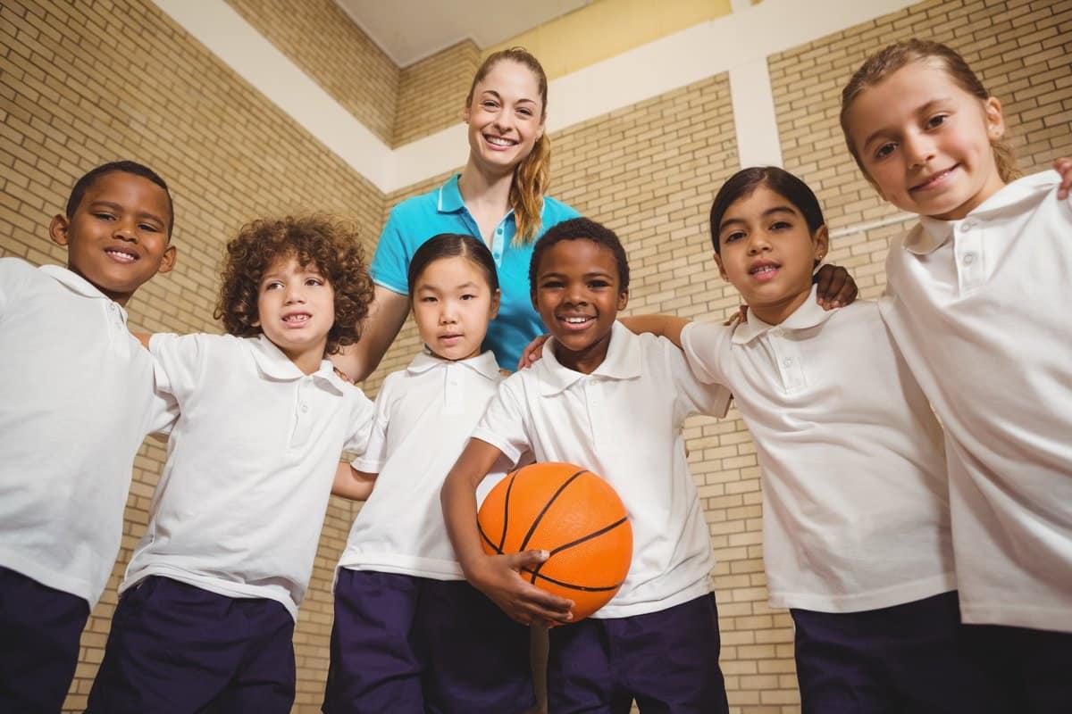 Oposiciones de Educación Física: Grupo de niños con una pelota de baloncesto y una profesora de educación física tras ellos.
