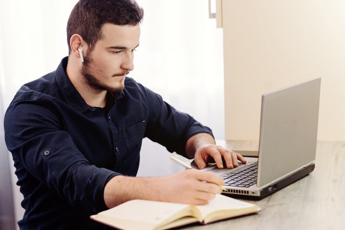 Un hombre estudiando para sus oposiciones de educación física con un ordenador portátil y un cuaderno.