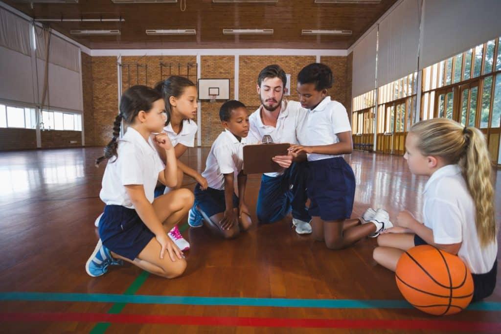 Un grupo de alumnos alrededor de su profesor de educación física repasando juntos.