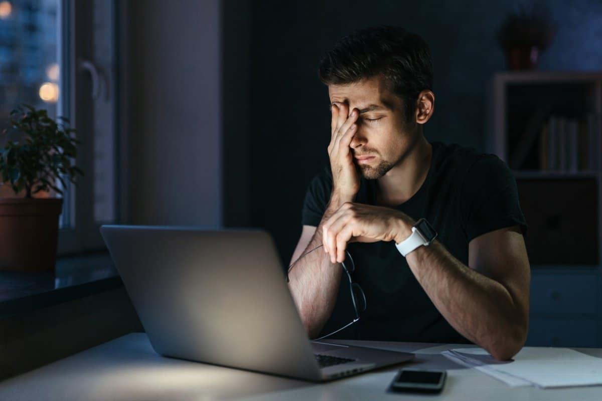 Hombre joven cansado de estudiar frente al ordenador