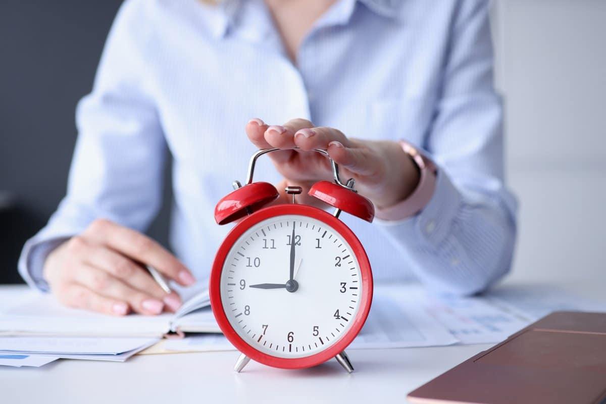 Mujer tocando con la palma de su mano la parte superior de un reloj que marca las 9 en punto.