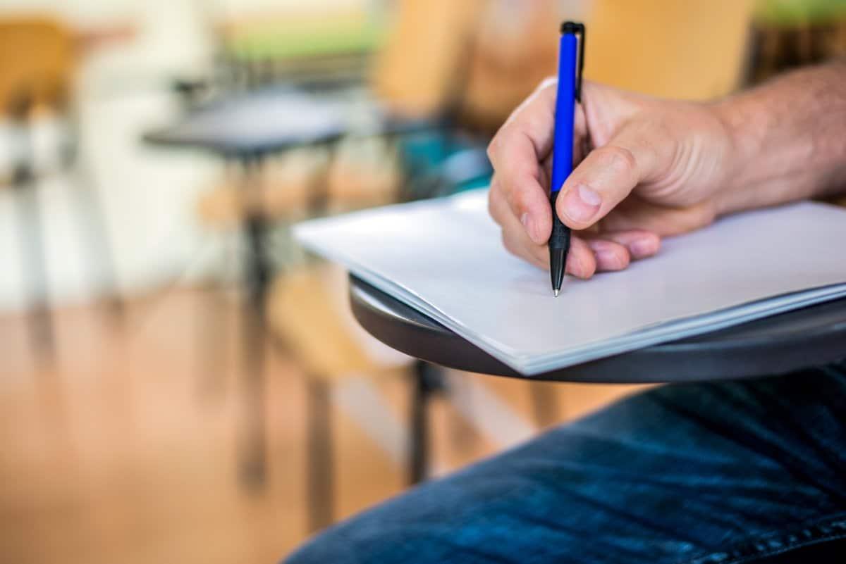 Hombre escribiendo en una hoja de papel sobre un pupitre en un aula.