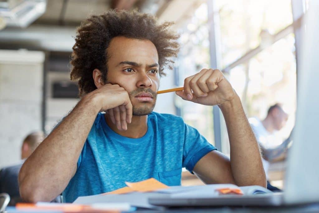 Hombre estudiando con rostro pensativo y preocupado.