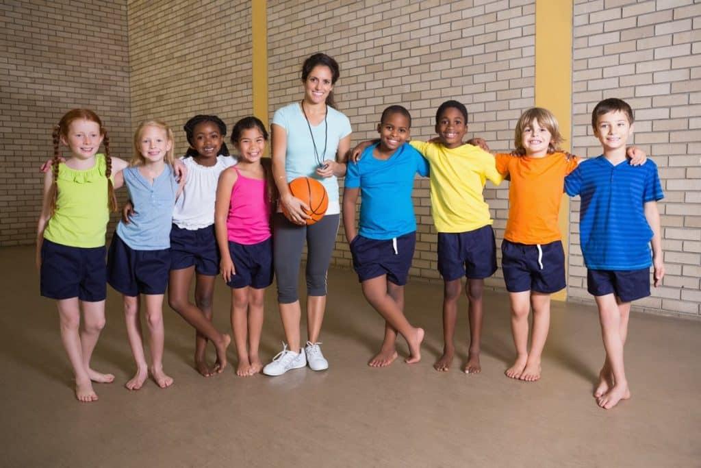 Grupo de alumnos sonriendo junto a su profesora de educación física de primaria
