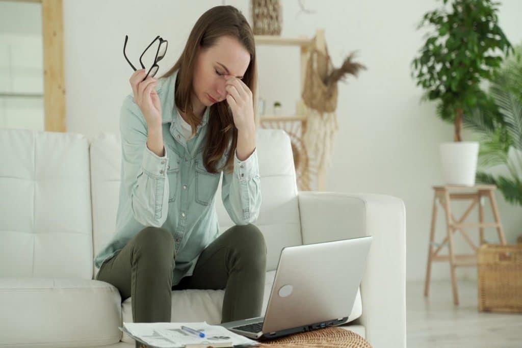 Mujer cansada frente al ordenador portátil quitándose las gafas y apretando con sus dedos entre sus ojos