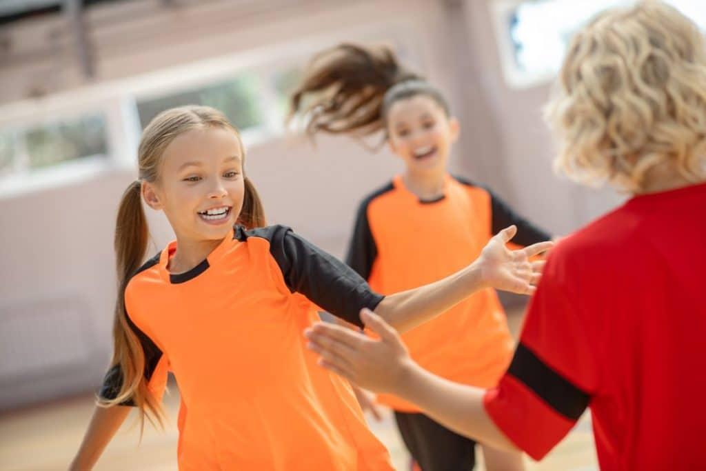 Niños y niñas jugando en un pabellón polideportivo