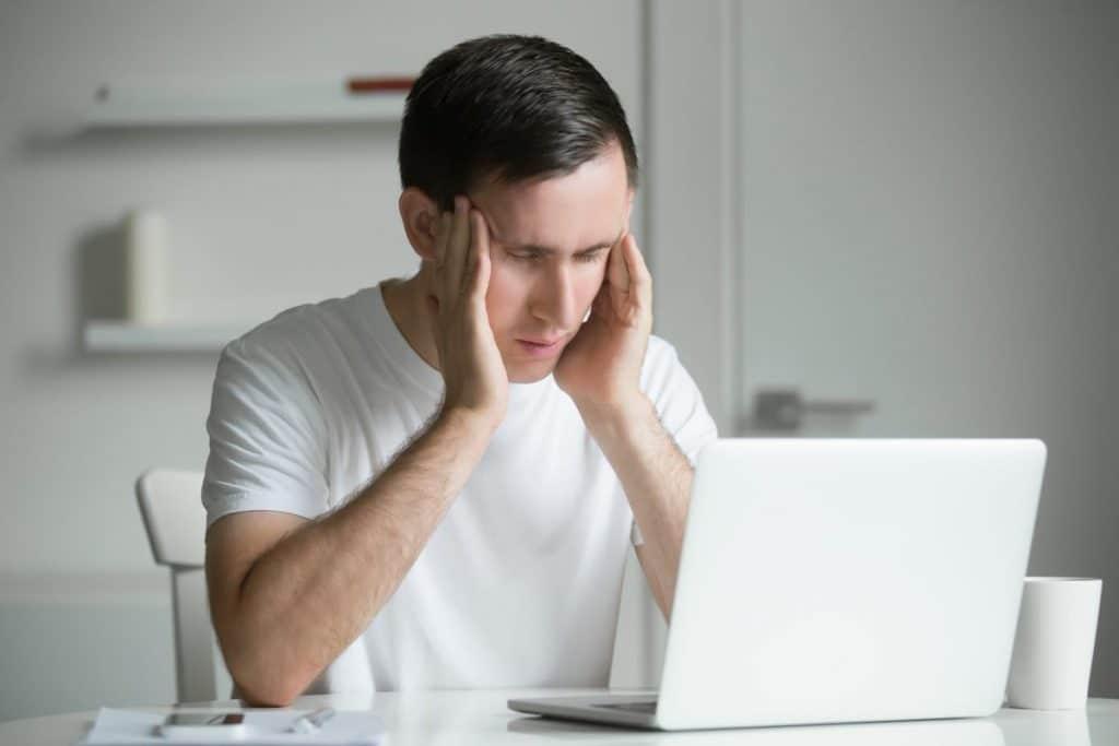 Hombre joven agobiado por el estrés de estudiar las oposiciones de Educación Física