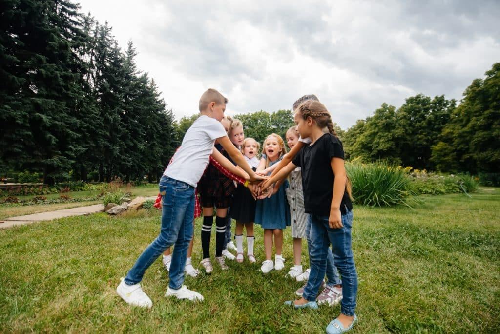 Niños en círculo juntando sus manos en el centro