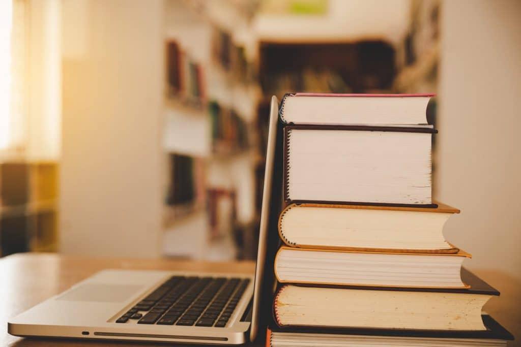 Ordenador portátil apoyado sobre una pila de libros sobre leyes de educación física