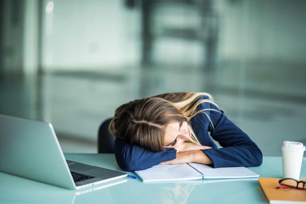 Mujer descansando sobre un cuaderno abierto y frente a un portátil
