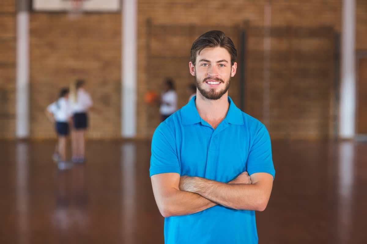 Profesor de educación física sonriendo y con los brazos cruzados.