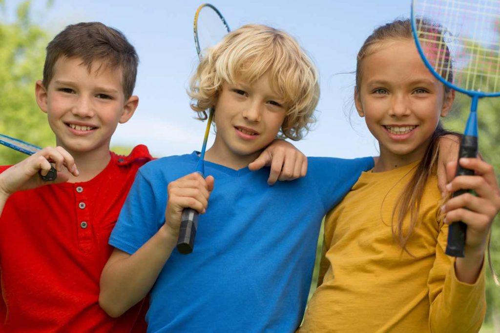 Tres niños cogidos por los hombros con unas raquetas de bádminton