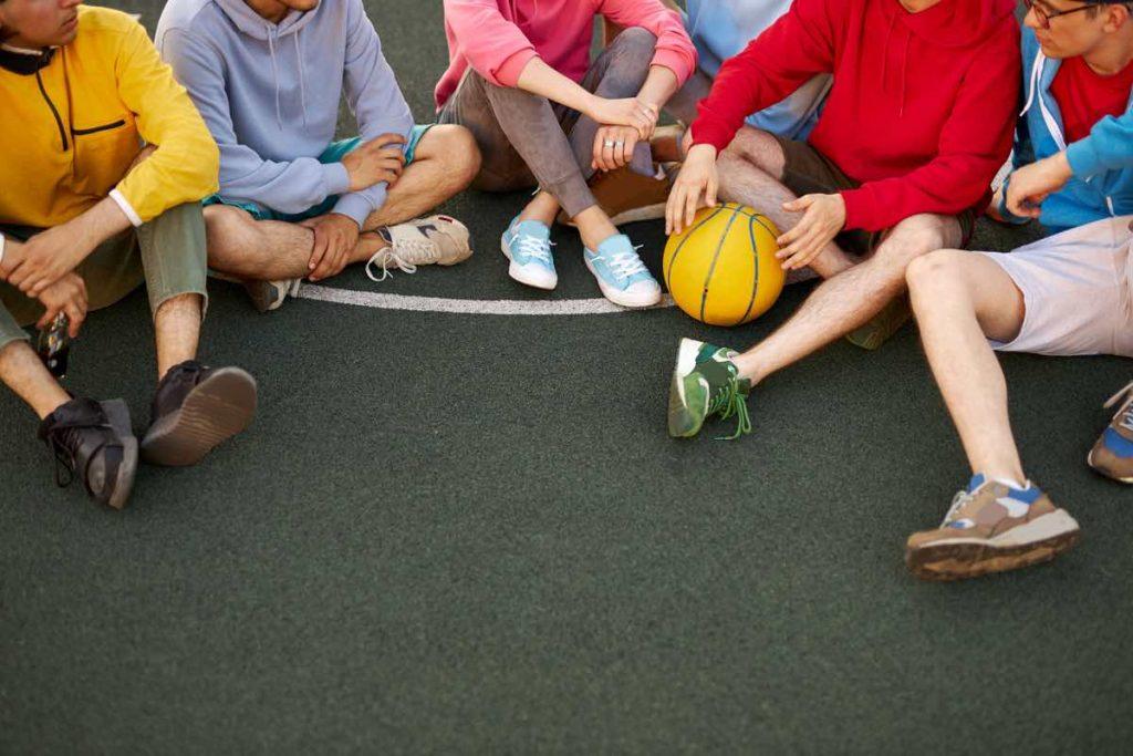 Chicos y chicas sentados en el suelo de una pista de basket