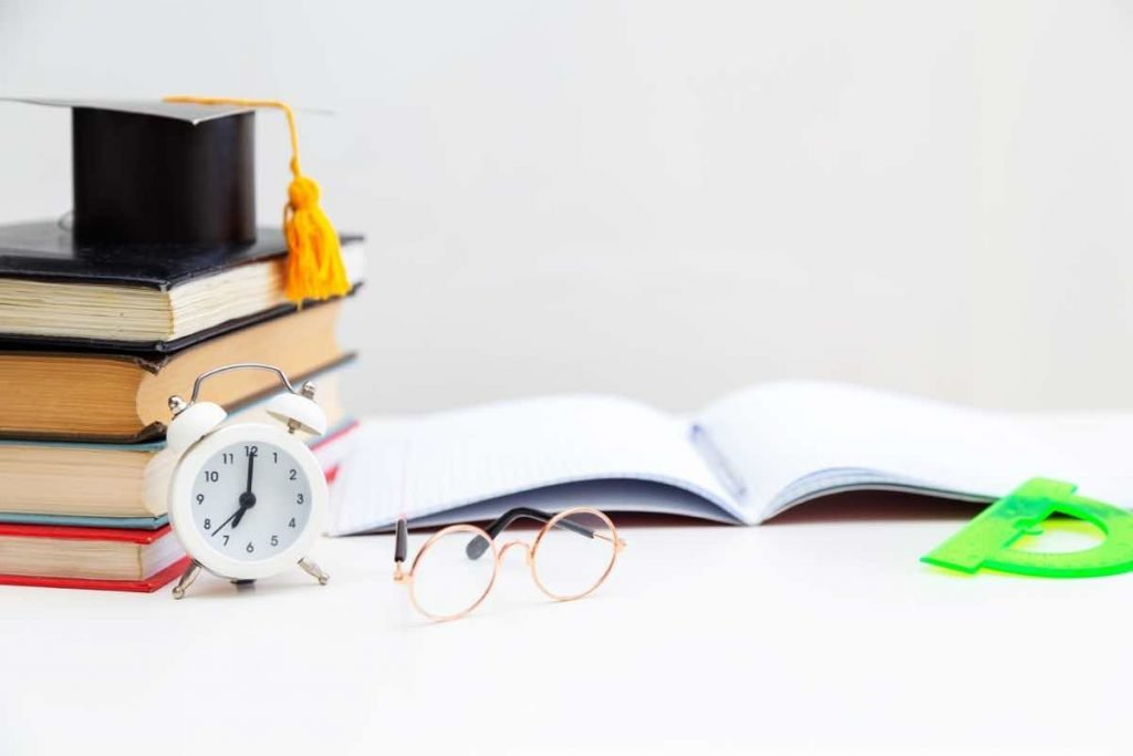 Libros, reloj de mesa y gafas sobre una mesa